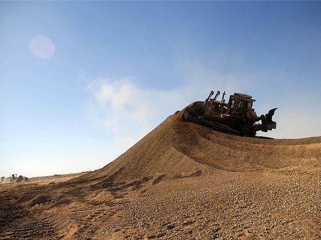 Bulldozer pushing dirt uphill